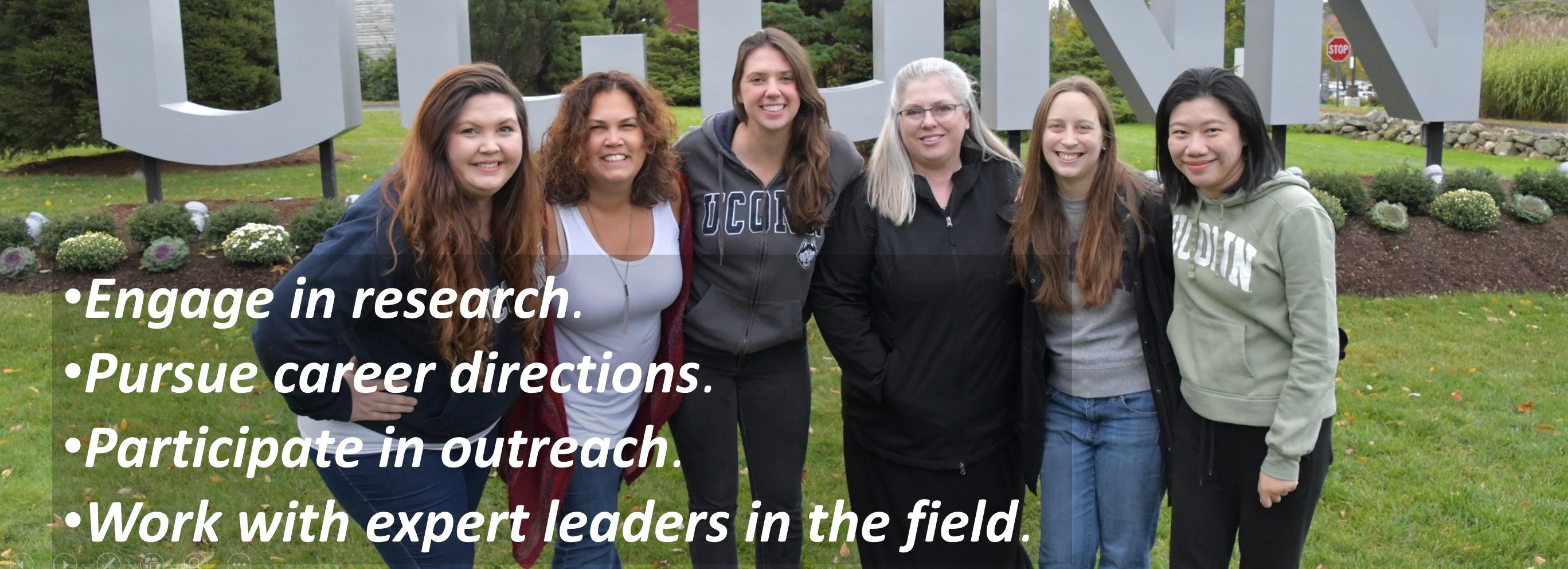 UConn Ph.D. Students in front of UConn sign with overlay of words saying Engage in research, pursue career directions, particpate in outreach, and work with expert leaders in the field.